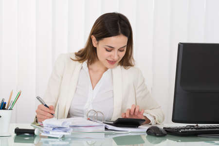 Photo Of Happy Businesswoman Calculating Bills In Office Stockfoto