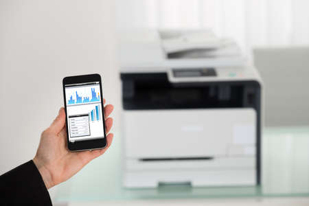 copier: Close-up Of Businesswoman Hand Giving Print Command On Smart Phone Stock Photo