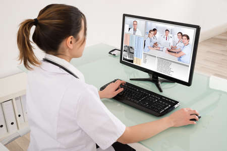 Young Female Doctor Video Conferencing With Medical Team On Digital Tablet