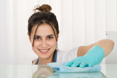 desk tidy: Close-up Of Happy Female Janitor Cleaning Desk With Rag