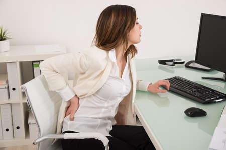 Empresaria joven que sufre de dolor de espalda en oficina
