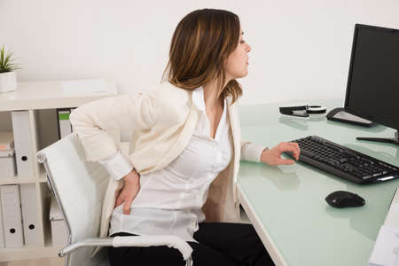 bad: Young Businesswoman Suffering From Backache In Office