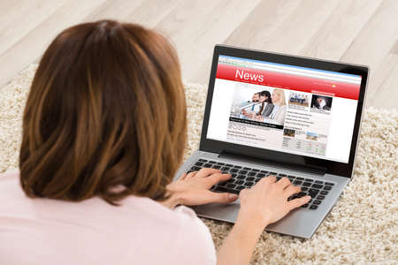 device: Woman Lying On Carpet Watching Online News Site On Laptop At Home Stock Photo