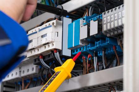 Man Elektricien onderzoeken Fusebox Met spanning Tester