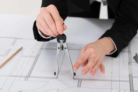 female architect: Close-up Of Female Architect Hands Holding Compass On Blueprint Stock Photo