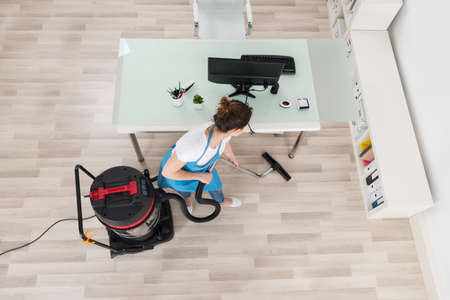 Young Female Janitor Cleaning Wooden Floor With Vacuum Cleaner Banque d'images