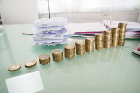 INVOICE: Stack Of Coins With Receipt In Paper Nail On Desk