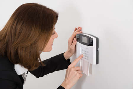 home security alarm: Close-up Of Woman Entering Code In Security System