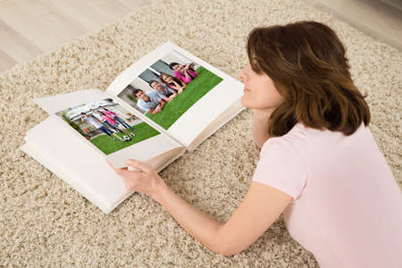 Young Woman Lying On Carpet Looking At Family Photo Album photo