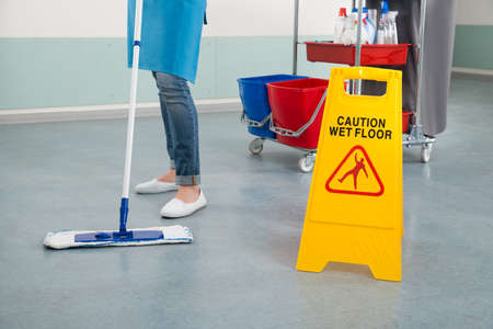 cleaning woman: Close-up Of Female Janitor Mopping Corridor With Caution Sign