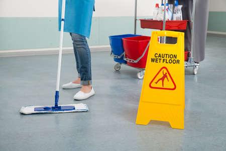 personal de limpieza: Primer De La Mujer conserje Corredor Mopping Con muestra de la precaución