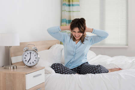 awakened: Exhausted Young Woman Awakened By An Alarm Clock In Her Bedroom Stock Photo
