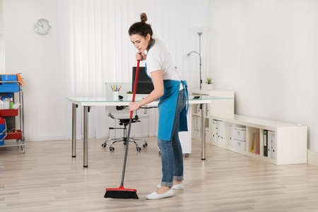 janitor: Young Female Janitor Sweeping Floor With Broom