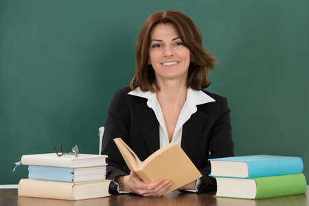 private schools: Happy Young Female Teacher Sitting At Classroom Desk
