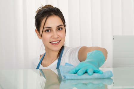 Close-up der glücklichen Frau Janitor Reinigung Schreibtisch mit Rag