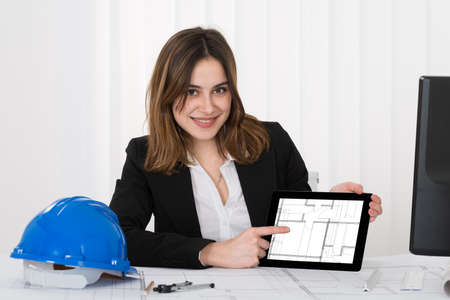 female architect: Happy Young Female Architect Pointing At Blueprint On Digital Tablet