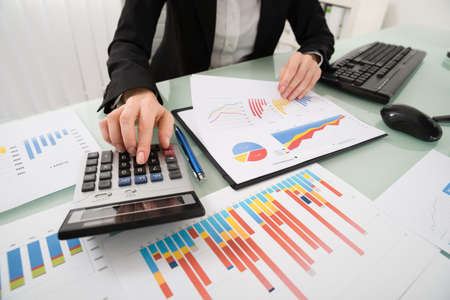 business chart: Young Businesswoman Analyzing Report On Chart With Calculator Stock Photo
