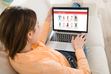 Junge Frauen-Einkaufen an der Laptop in ihrem Zimmer