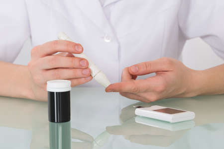 glucometer: Close-up Of Female Hand Checking Blood Sugar Level With Glucometer