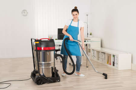 vacuum cleaner: Female Janitor Cleaning Floor With Vacuum Cleaner In Office Stock Photo