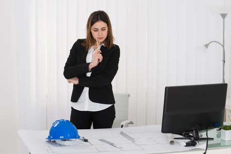 female architect: Young Female Architect Working On Blue Print In Office Stock Photo