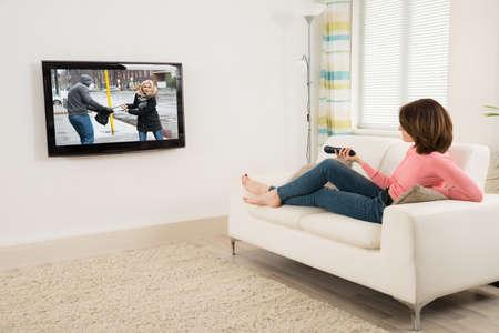 Joven acostado en el sofá, manteniendo a distancia mientras ve la televisión