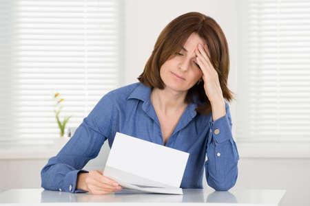 Sad junge Frau liest Dokument in Office Standard-Bild