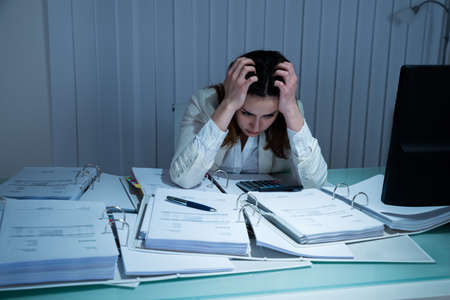 woman in pain: Stressed Young Businesswoman Working Late In Office