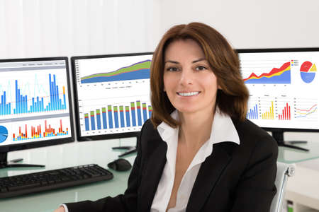 multiple: Happy Young Businesswoman With Graphs On Multiple Computers In Office