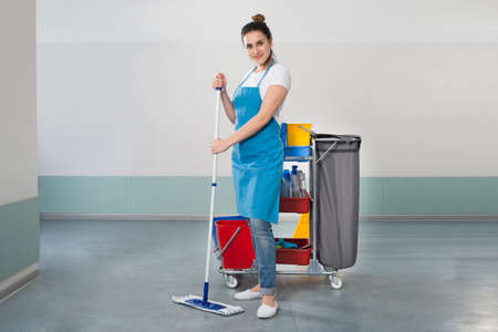 cleaning services: Happy Young Female Janitor With Cleaning Equipment