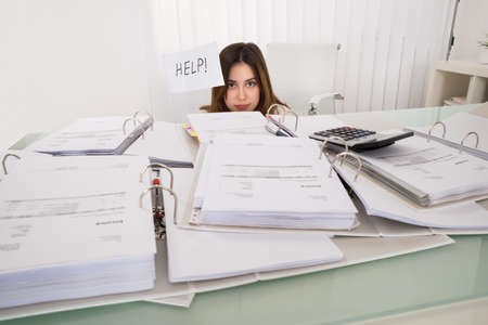 stressed business woman: Unhappy Young Businesswoman Holding Flag With The Text Help In Office Stock Photo