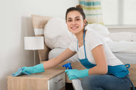 Happy Female Housekeeper Cleaning Nightstand In Room Archivio Fotografico