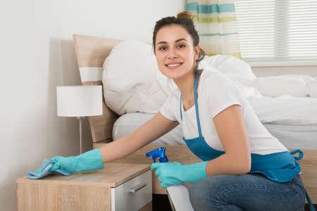 orden y limpieza: Mujer feliz ama de casa de limpieza Mesilla de noche en la habitación Foto de archivo