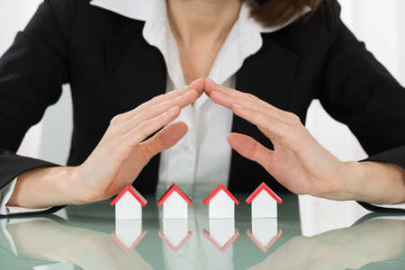 sheltering: Close-up Of Businesswoman Hand Sheltering House Models