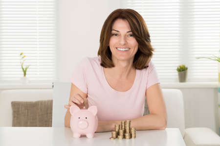 inserting: Smiling Young Woman Inserting Coin In Piggybank In Front Of Stacked Coins Stock Photo