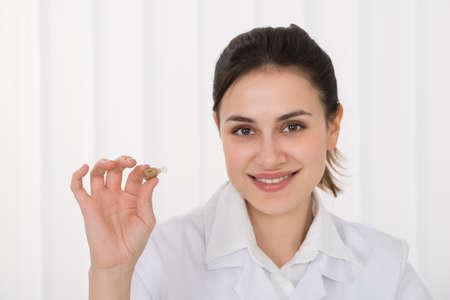 Retrato de la prótesis de oído femenino joven feliz del doctor Holding