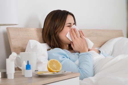 Giovane donna infettata da freddo che soffia il naso nel fazzoletto