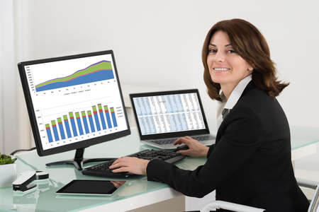 Businesswoman Checking Financial Report On Computer With Digital Tablet And Laptop On Desk photo