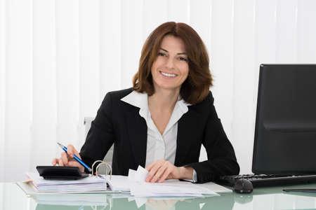 Glückliche Geschäfts Berechnung Steuer am Schreibtisch im Büro