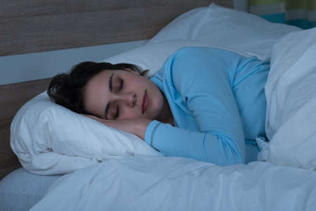 Young Woman Sleeping On Bed In Her Bedroom