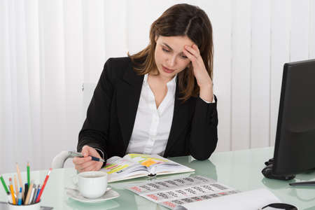 event planner: Tired Young Businesswoman Writing Schedule In Diary With Calendar On Desk