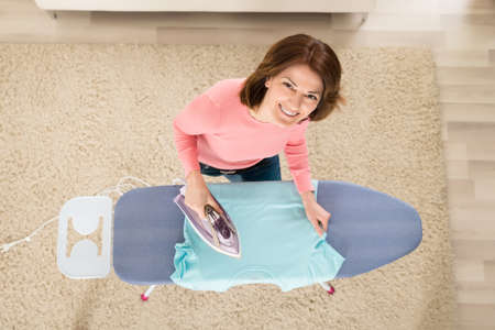 woman ironing: Young Woman Ironing Clothes With Steam Iron At Home Stock Photo