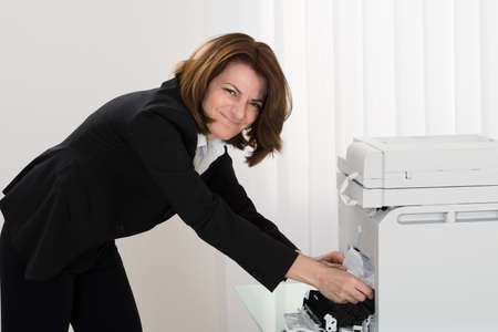 photocopy: Young Businesswoman Removing Paper Stuck In Photocopy Machine At Office Stock Photo