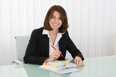 event planner: Happy Young Businesswoman With Calendar Writing Schedule In Diary