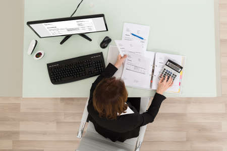 calculating: Businesswoman Sitting In Office Calculating Financial Report