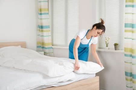 Young Female Housekeeper Arranging Bedsheet On Bed In Room Stock Photo