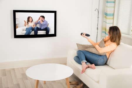 mujer sentada: Mujer joven que se sienta en el sofá Televisión de observación
