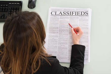job hunt: Young Businesswoman Holding Pen While Reading Newspaper Stock Photo