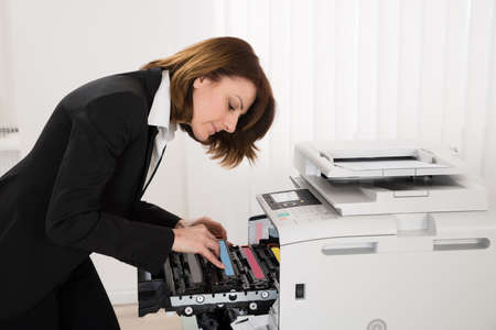 toner: Young Businesswoman Fixing Copy Machine In Office Stock Photo