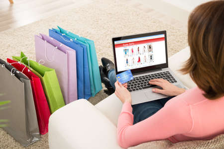 buy online: Young Woman On Sofa Shopping Online With Debit Card